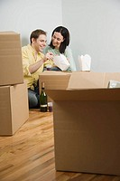 Couple eating take out on boxes in new house