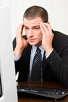 Businessman with hands on forehead looking at pc_screen, close_up, portrait