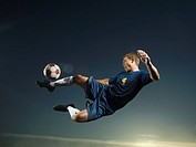 Man kicking soccer ball in air