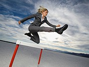 Businesswoman jumping over hurdle, Salt Flats, Utah, United States