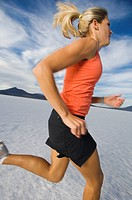 Woman running on salt flats, Utah, United States