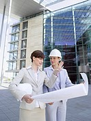 Germany, Baden_Württemberg, Stuttgart, two businesswomen with hard hats discussing building plan