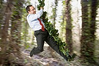 Hispanic businessman swinging on forest vine