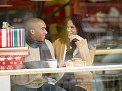 African couple with presents in coffee shop