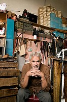 Senior Hispanic male cobbler sitting in workshop