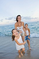 Multi_ethnic mother and daughters playing in surf