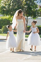 Multi_ethnic bride holding hands with flower girls