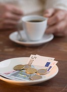 Euros on plate at cafe