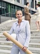 Germany, Baden_Württemberg, Stuttgart, Businesswoman with roll, businesspeople in background