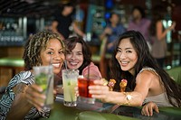Multi_ethnic friends drinking cocktails in nightclub