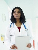 Indian doctor in lab coat holding medical chart