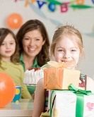 Girl holding stack of birthday gifts