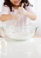 Hispanic girl mixing dough