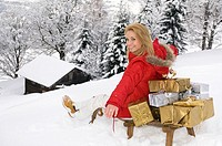 Austria, Salzburger Land, Altenmarkt, Young woman sitting on sledge brimming with Christmas presents