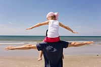 Germany, Baltic sea, Father carrying daughter 6 on shoulders, rear view