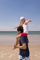 Germany, Baltic sea, Father carrying daughter 6 on shoulders