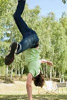 Germany, Young man performing handstand on one hand