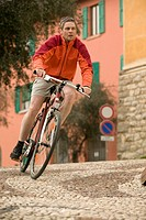Italy, Lombardy, Campione, Man mountain biking through village