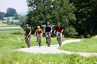 Germany, Bavaria, Oberland, Four mountainbikers riding across path