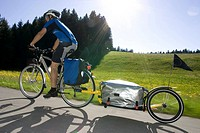 Germany, Bavaria, Man riding mountainbike with trailer