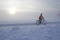 Germany, Bavaria, Oberland, Man mountain biking across snow_covered path