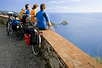 Italy, Tuscany, Monte Argentario, Mountainbikers looking on to the sea