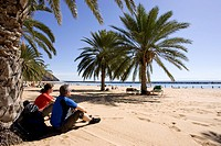 Spain, The Canary islands, Teneriffa, Couple relaxing on palm beach