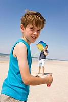 Germany, Baltic sea, Father with son 8_9 flying kite on beach