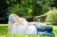 Germany, Bavaria, Munich, Young woman relaxing in meadow