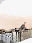Businesswoman leaning on lobby railing