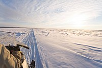 Snowmachiner following trail on frozen snow covered Kuskokwim River Western Alaska Winter