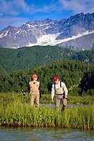 Man & woman fly_fishing for salmon on Big River Lakes with Chigmit Mountains in the background in Southcentral Alaska during Summer