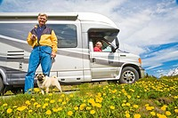 Mature couple & RV parked with their pet dog in a scenic pullout view scenery near Summit Lake alongside the Seward Highway on the Kenai Peninsula, Al...