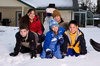 Alaskan native children building snowman together outside Alaska winter