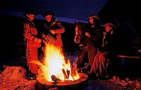 Group of cowboys and cowgirls sitting around a campfire at night in Saskatchewan Canada