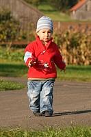 Kleinkind spaziert durch den Herbst