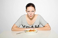 Young woman eating pasta