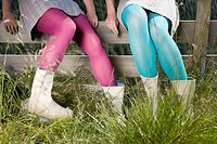 Girls wearing tights sitting on a fence