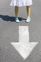 Woman standing on a direction arrow