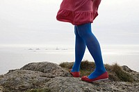 Woman in blue tights standing on rocks