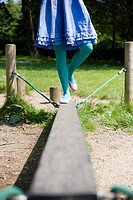 Woman walking on a plank in a playground