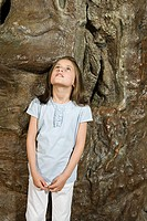 Girl standing by a fake tree trunk