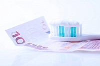 Zahnbürste auf Geldschein