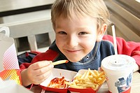 CHILD EATING A MEAL Model. 6_year_old boy in a fast food restaurant.
