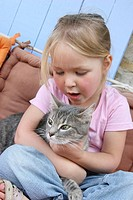 CHILD WITH ANIMAL Girl and 1_year_old female cat European breed.