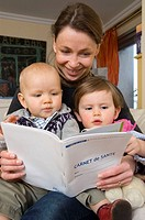 FAMILY INDOORS A mother is looking at the health record of her two children aged of 11 months and 2 years and a half.