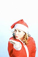 Happy young woman in Santa´s suit blowing snow