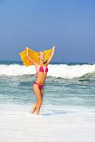 Cheerful young woman holding towel on beach