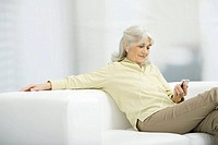 Senior woman listening to MP3 player, sitting on couch