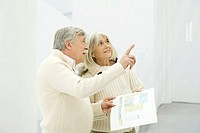 Senior couple standing together, man holding floor plans and pointing up